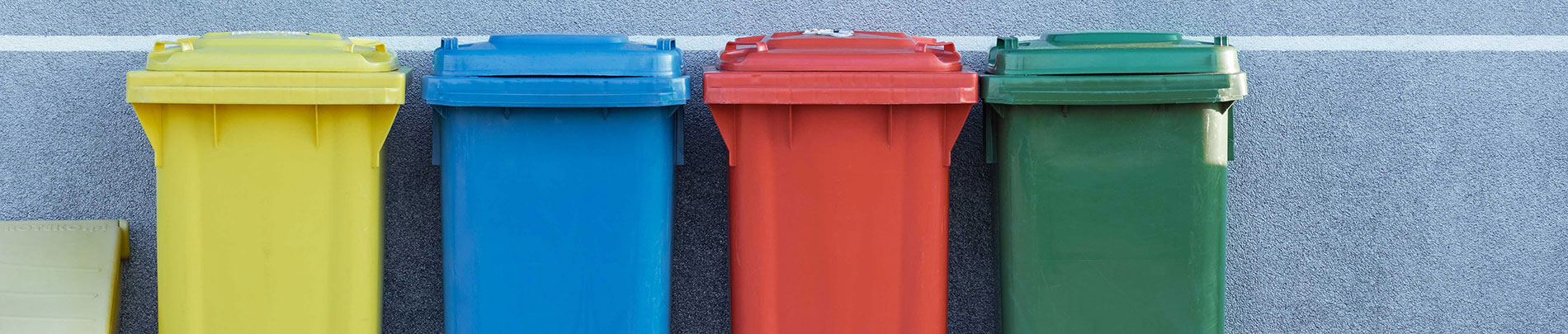 A series of colourful garbage and recycling bins lined up against a wall.