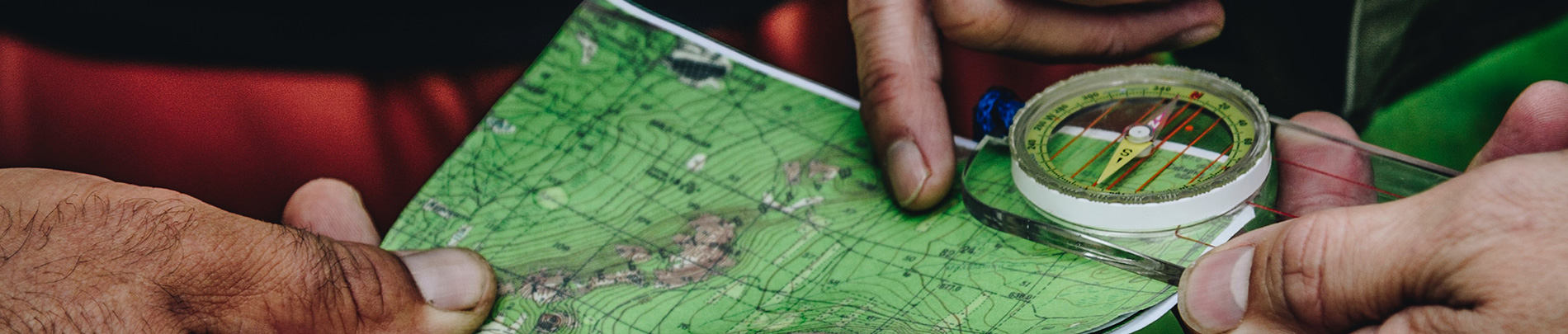 Hands hold a topographic map and compass.