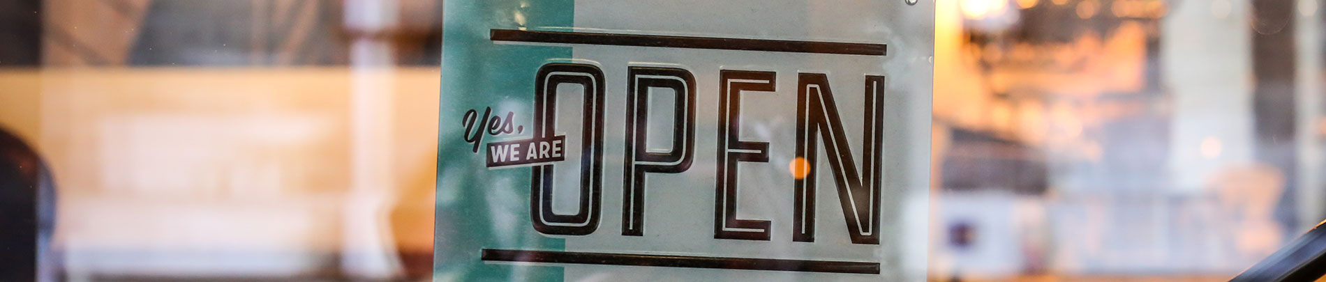 An open sign hanging in a shop window.
