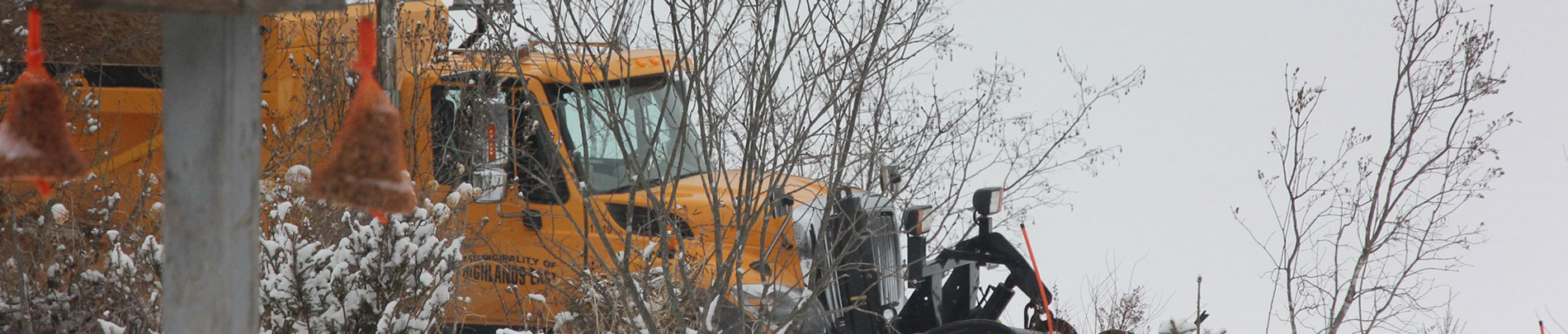 A Highlands East snow plow drives by plowing snow off the road.