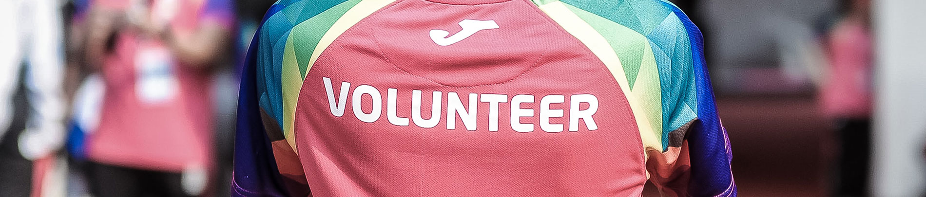 A person wearing a colourful t-shirt that says volunteer across the back.