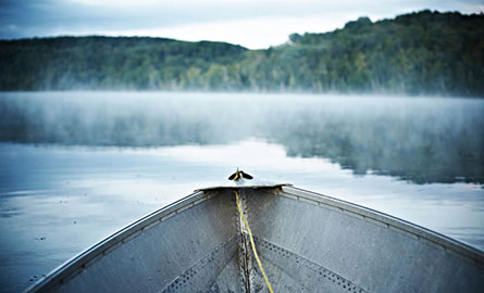 The view from a small boat on a misty lake.