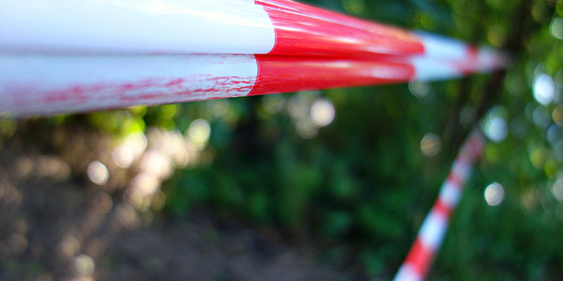 Red and white barricade tape blocking access to an outdoor location.