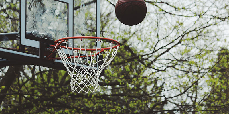 A basketball being thrown into a hoop.