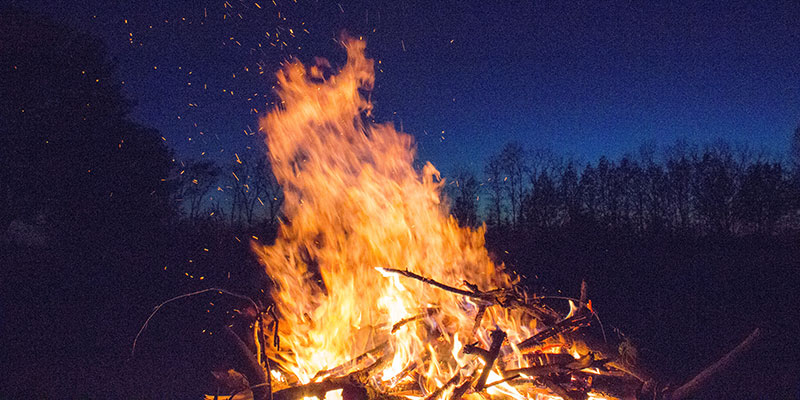 A large bonfire burns in the night.