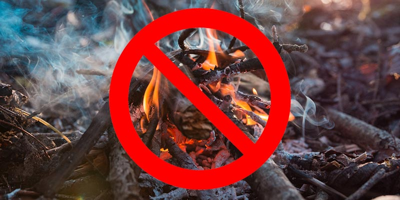 A crossed-out circle superimposed over a photo of an outdoor fire to convey that no burning of any kind is allowed.