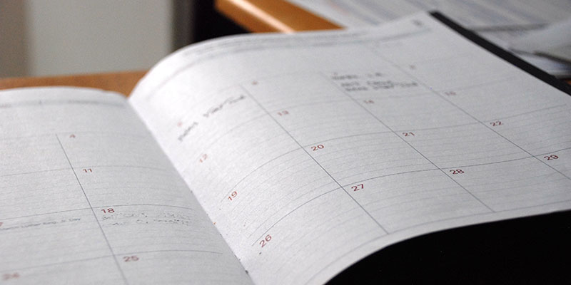 An open calendar book on a table.