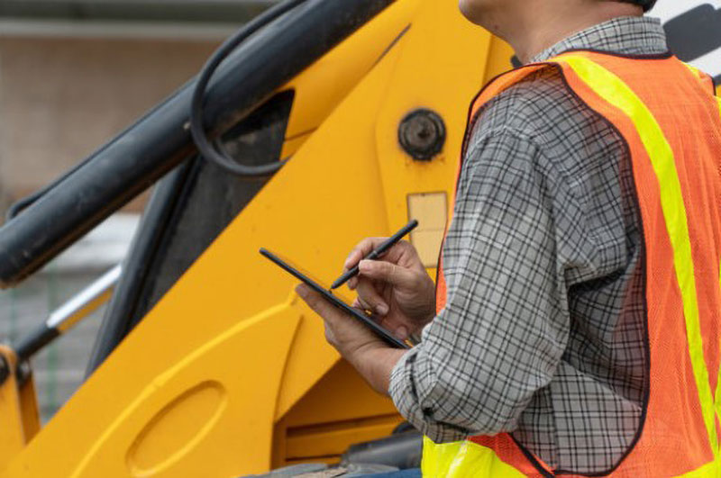 Person in front of backhoe using ipad.