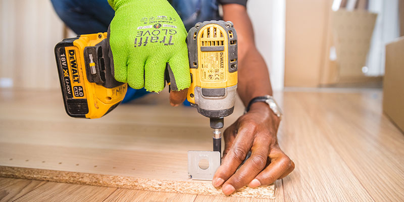 Person using a impact driver to fasten down some wood.