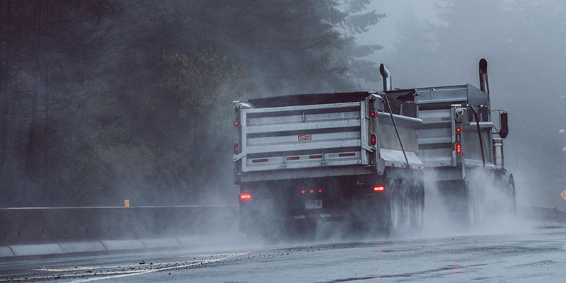 A loaded truck and trailer travelling on a rainy road.