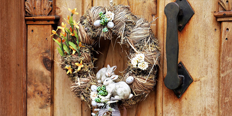 An easter wreath hangs on the outside of a door.