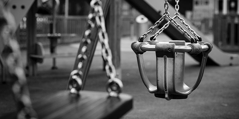 black and white photo of empty swings at an empty playground