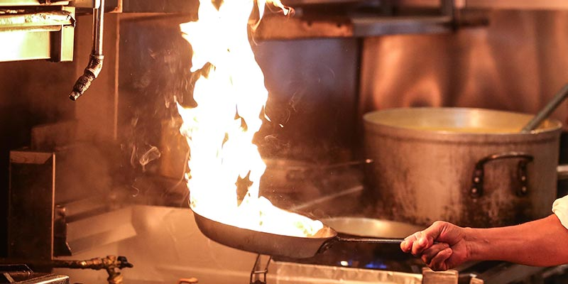 A flaming pan in the kitchen.