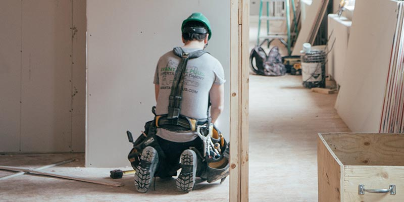 A person kneels to work on the floor of a home being renovated.
