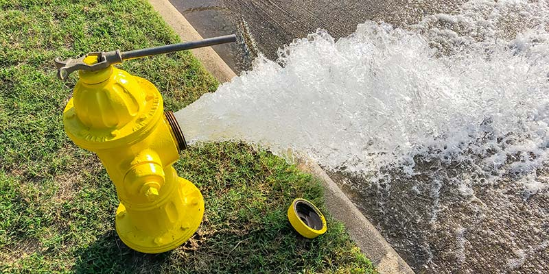 A yellow hydrant with water flowing out of it.