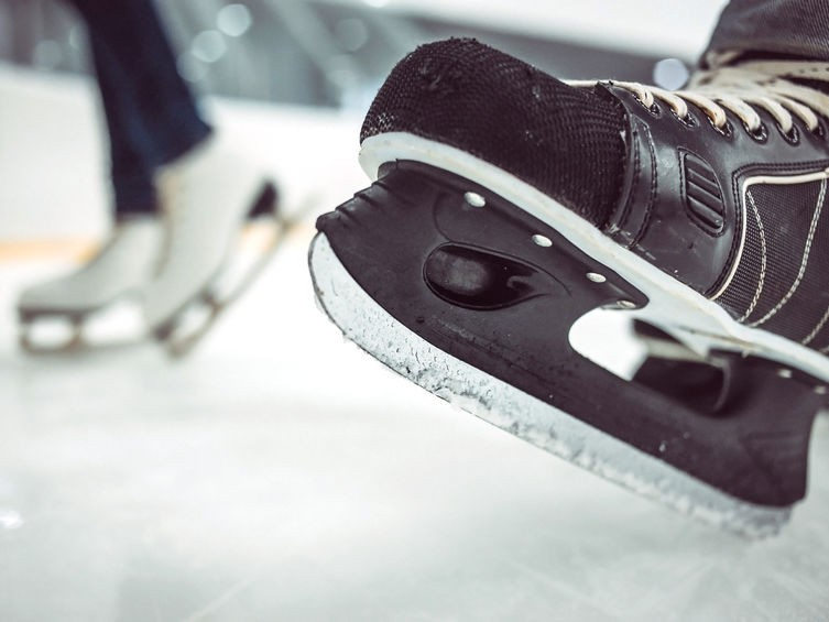 A close up photo of some ice skates on the rink.