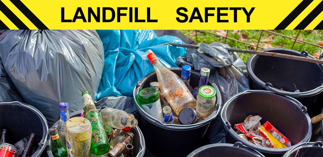 Yellow caution sign that reads landfill safety in front of a collection of garbage.