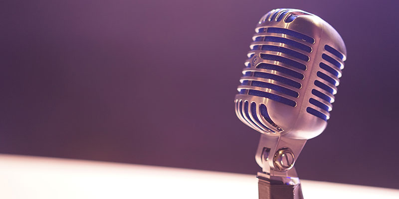 A silver condenser microphone stands in front of a plain background.