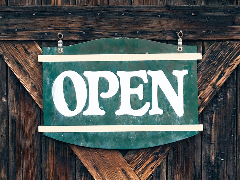 A green open sign hangs on a wooden door.