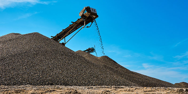 A gravel pile being made by a crusher's conveyor belt.