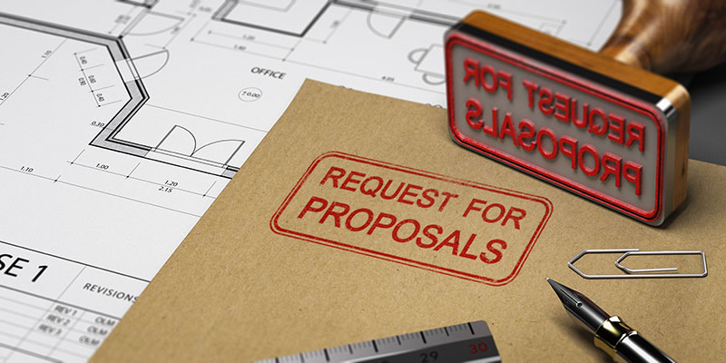 A folder stamped with Request for Proposal sits on a desk