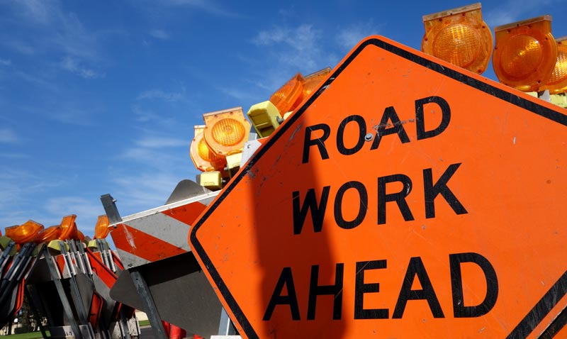 A close up of an orange sign that reads road work ahead.