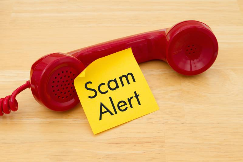 A phone handset sitting on a table with a sticky note on it that reads scam alert.