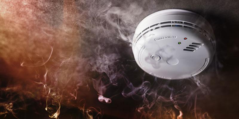 A smoke alarm beeps as smoke and flames surround it.