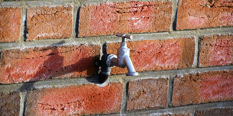 A water tap on the side of a building.