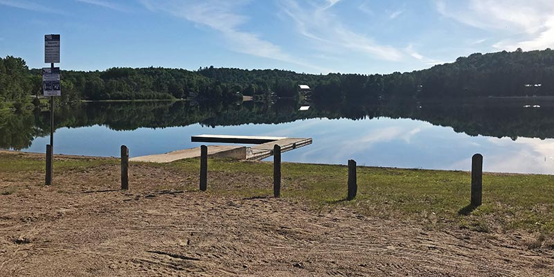 The dock and beach at Wilbermere lake on a calm summer morning.