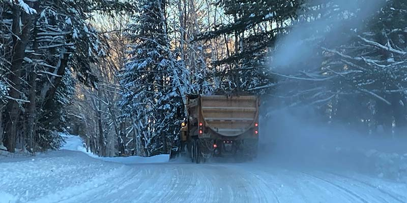 A snow plow clearing a snowy road.