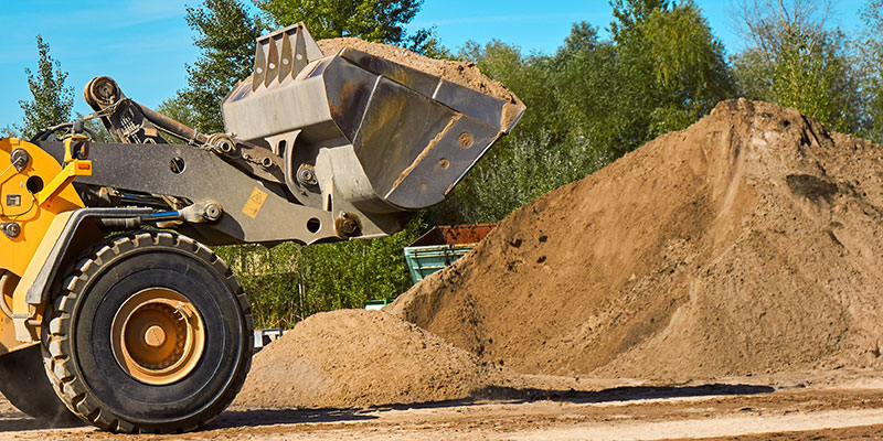 A front end loader scooping up a bucket of sand from a large pile.